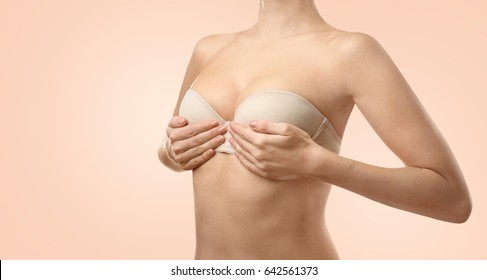 Woman on color background. Breast correction and plastic surgery concept