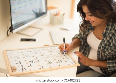 Woman on computer desk writing on a calendar