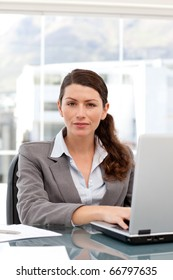 Woman on the computer looking at the camera in an office