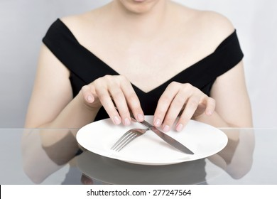 Woman on diet, dining in front of empty plate