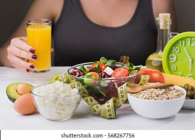 Woman on a diet. healthy and proper food with salad and dairy product on wooden table. Glass of juice in hand.