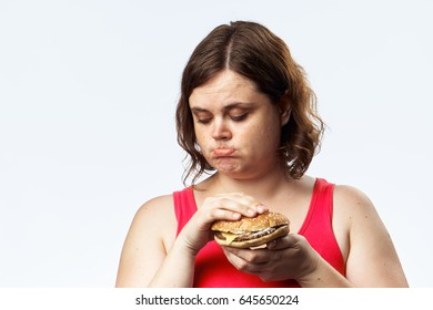 Woman on a diet, woman is sad with a burger in her hands