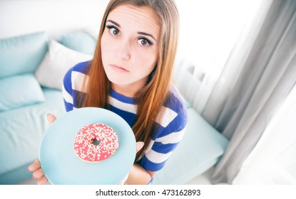Woman on diet with unhealthy donut thinking about eating it