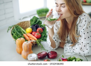 Woman on a diet. Young and happy woman eating healthy salad sitting on the table with green fresh ingredients indoors. High quality photo