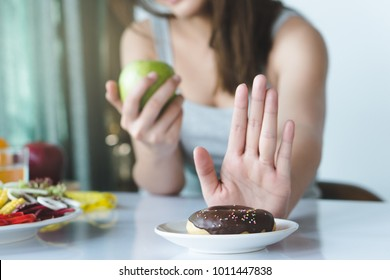 Woman on dieting for good health concept. Close up female using hand push out her favourite donut and choose green apple and vegetables for good health.