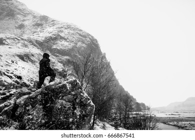 Woman on edge of cliff in the Scottish Highlands in the snow