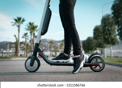 Woman on an electric scooter on the road. The concept of ecological transport in the city.