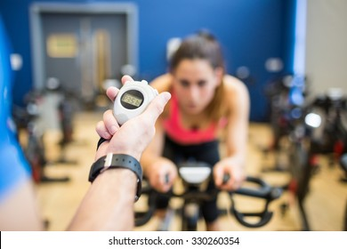 Woman on exercise bike with trainer timing her at the gym