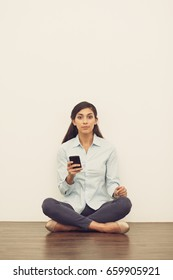 Woman on Floor in Lotus Pose with Smartphone