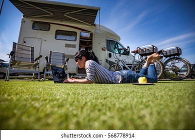 Woman on the grass, looking at the laptop near the camping. Caravan car Vacation. Family vacation travel, holiday trip in motorhome