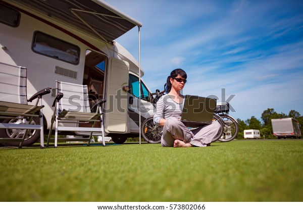 Woman on the grass, looking at the laptop near the camping . Caravan car Vacation. Family vacation travel, holiday trip in motorhome
