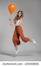 woman on a gray background jumping. Woman with long curly hair. Woman with a balloon in hand. Fashion woman in orange trousers