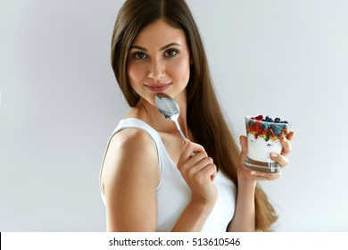 Woman On Healthy Diet. Closeup Of Beautiful Cheerful Girl With Glass Of Natural Yogurt, Delicious Berries ( Blueberry, Goji, Raspberries ) And Oatmeal, Granola. Organic Nutrition. High Resolution
