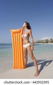 woman on a heavenly beach with an orange air mattress