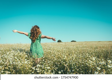 woman on her back with open arms in a field of daisies