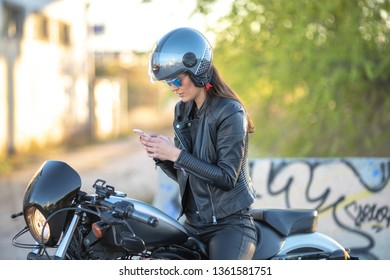 woman on her motorcycle and mobile phone