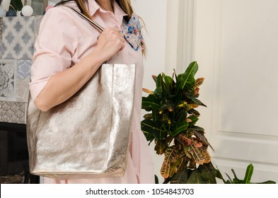 woman on her shoulder has a large capacious pearly fashion bag. Trendy large bag with a metallic glow
