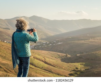 Woman on the hill taking a picture in Betancuria, Fuerteventura, Canary Islands, Spain.
