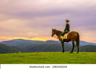 A woman on horseback admiring the scenery in the Australian countryside,