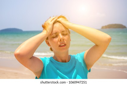 Woman on hot beach with sunstroke. Health problem on holiday. Medicine on vacation. Dangerous sun. Beach life. Sunstroke on sunny beach. Girl on beach. Health threat on vacation. Holiday health care