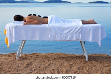woman on hot stone massage table by the sea
