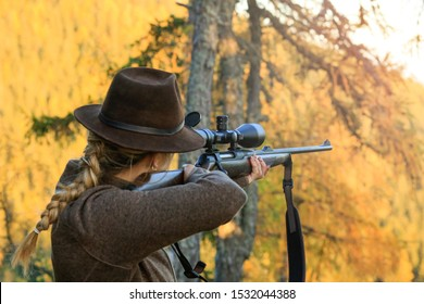 Woman on the hunt looks into the rifle, waiting for the deer during the autumn