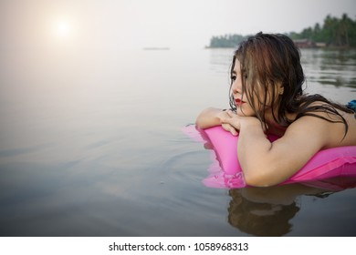 Woman on inflatable swimming pool bed enjoying sun tanning. Summer vacation bikini girl. Woman relaxing on pink air mattress bed floating on raft in the sea.