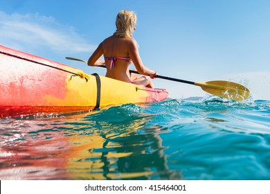 Woman on kayak in ocean with blue sky background