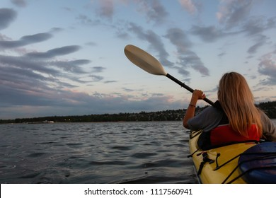 Woman on a kayak is paddling in the ocean during a vibrant sunset. Taken in Vancouver, British Columbia, Canada.