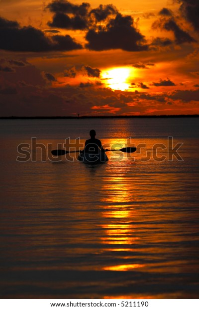woman on a kayak watching the sunset