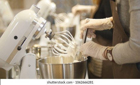 Woman on the kitchen near electric mixer ready for cooking