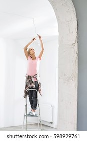 Woman on ladder fitting light bulb in new house