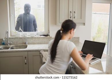 Woman on laptop in kitchen being observed by burglar through window