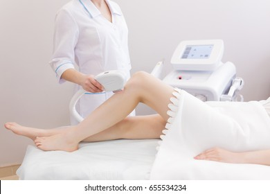 Woman on laser hair removal procedure at beauty salon. Epilation and Photoepilation concept