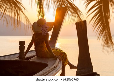Woman on a long tail boat at sunset in Thailand