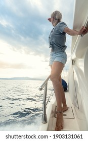 Woman on luxury yacht looking forward at seascape.