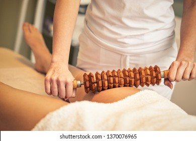 Woman on maderotherapy anticellulite massage treatment  of leg at beauty spa salon