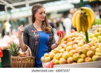 Woman on market store buying apple