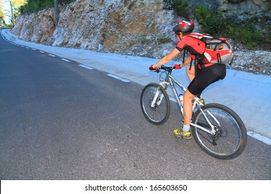 Woman on a mountain bike cycling and ascending a mountain road