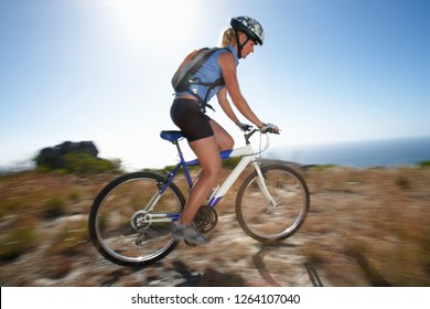 Woman on mountain bike riding at speed on rough ground near ocean on active vacation with motion blur and sunshine lens flare