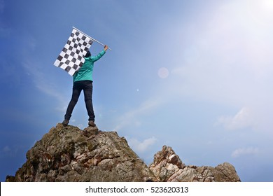 woman on a mountain peak Businessman's vision is defined by pointing to the target checkered flag on the high peaks.