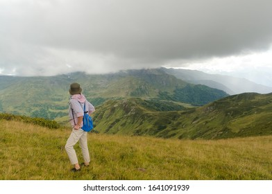 Woman on the mountain side under low clouds. A mountain valley in the Caucasian mountains. The far mountain peak is covered with dense clouds. The rain will begin in a few minutes