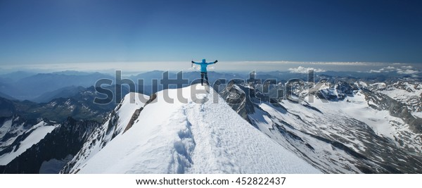 Woman on a mountain summit, moment of a success, reaching a top of a mountain