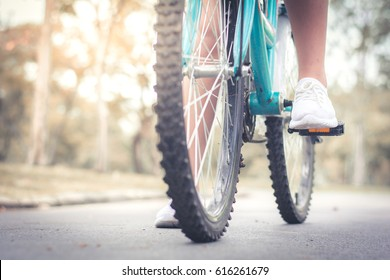 Woman on old  bicycle with back light - Close up of girl feet riding vintage bike in park outdoor for fall time - Vintage fashion concept - Focus on top foot - Warm retro filter