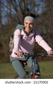 woman on a park track with a mountain bike in a sunny day