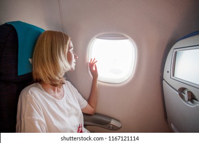 Woman on passenger seat near window in airplane