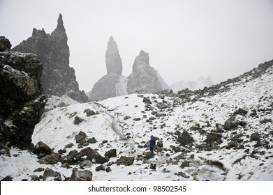 Woman on path in snow storm on the Old Man of Storr.