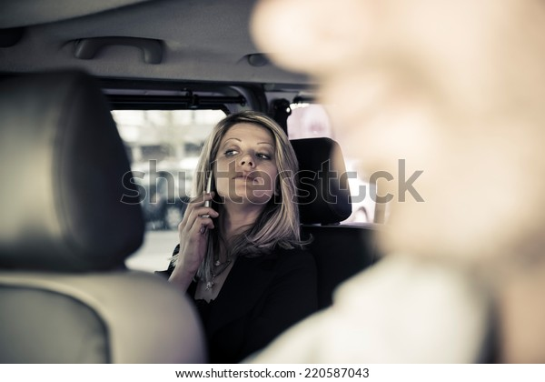 Woman on the phone inside a taxi
