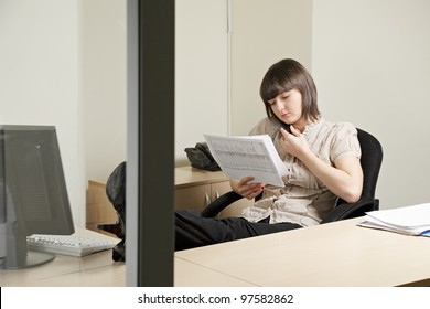 Woman on phone working with documents in office