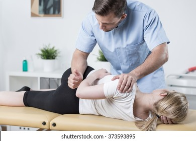 Woman on physiotherapy table lying on the side